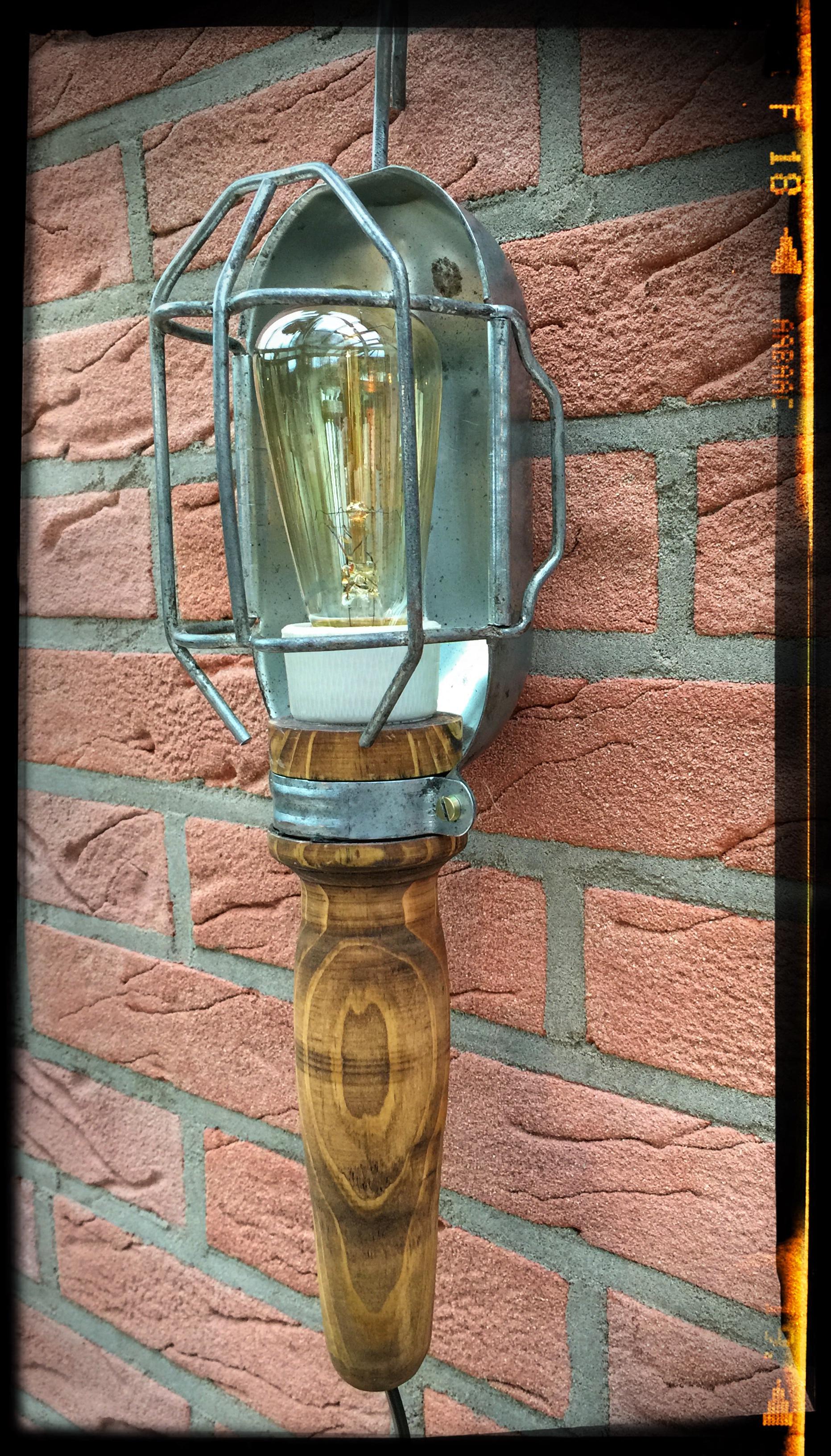 Zur Wandleuchte aufgearbeitete alte Baulampe